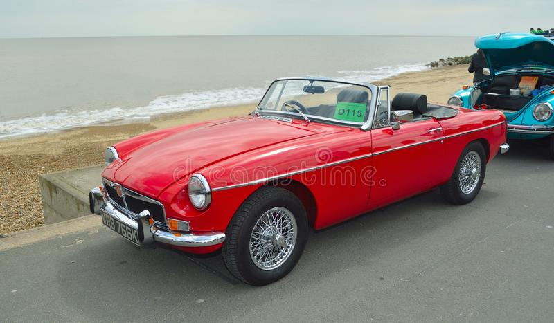 FELIXSTOWE, SUFFOLK, ENGLAND - MAY 07, 2017: Classic Red Triumph Spitfire Convertible Motor Car Parked on Seafront Promenade. royalty free stock photo