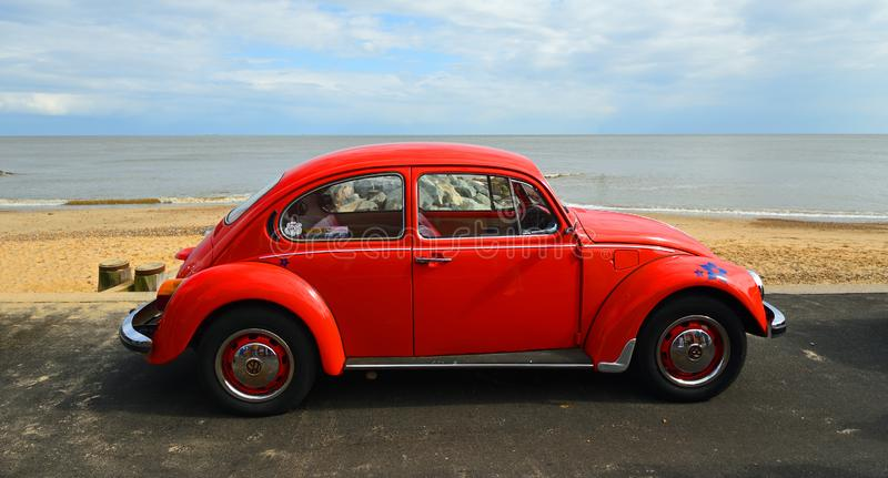 Classic Red  Volkswagen Beetle parked on seafront promenade with sea and beach in background. royalty free stock photos