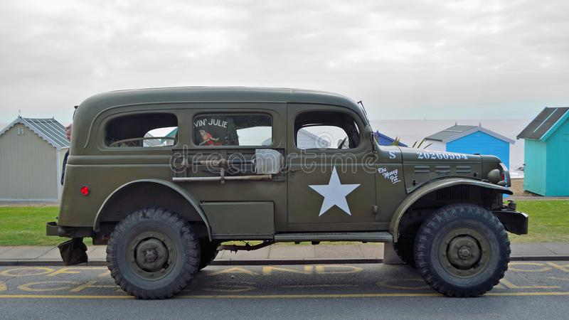 Vintage American Military Vehicle Parked on Seafront Promenade in front of Beach Hut. royalty free stock image