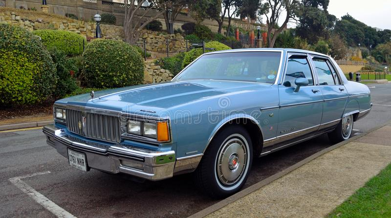 Classic Pontiac Parisienne V6 Parked with gardens in background. stock photos