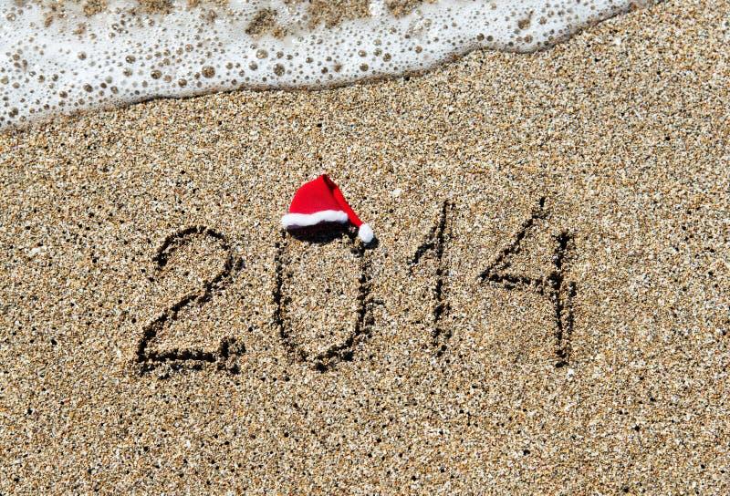 Feliz Año Nuevo 2014 con el sombrero de la Navidad en la playa arenosa - día de fiesta foto de archivo