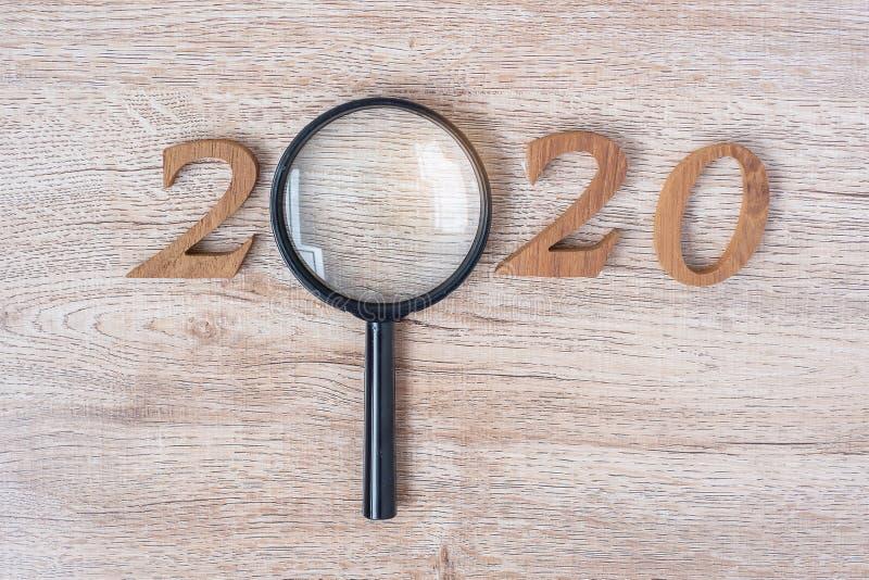 2020 Feliz Año Nuevo con Empresario sosteniendo la lupa de cristal y el número de madera sobre la mesa. Nuevo comienzo, visión, fotos de archivo libres de regalías