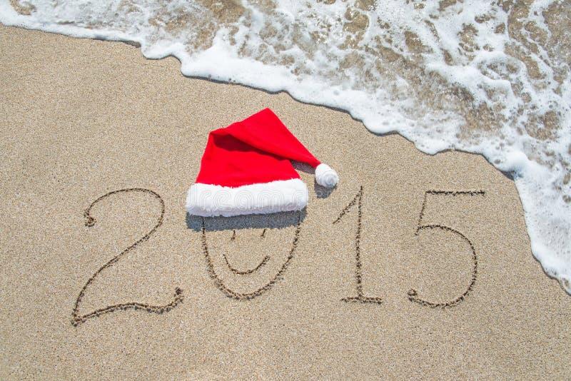 Feliz Año Nuevo 2015 con la cara sonriente en el sombrero de santa en la playa arenosa foto de archivo libre de regalías