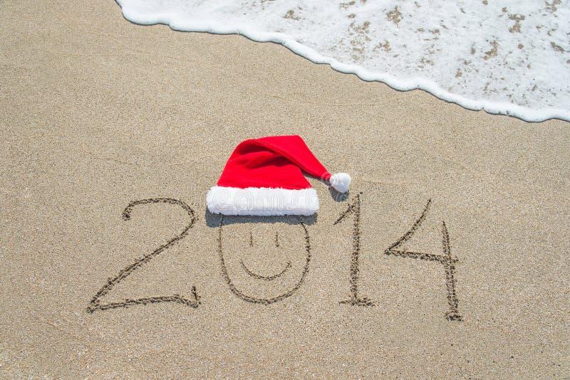 Feliz Año Nuevo 2014 con la cara sonriente en el sombrero de santa en la playa arenosa imágenes de archivo libres de regalías