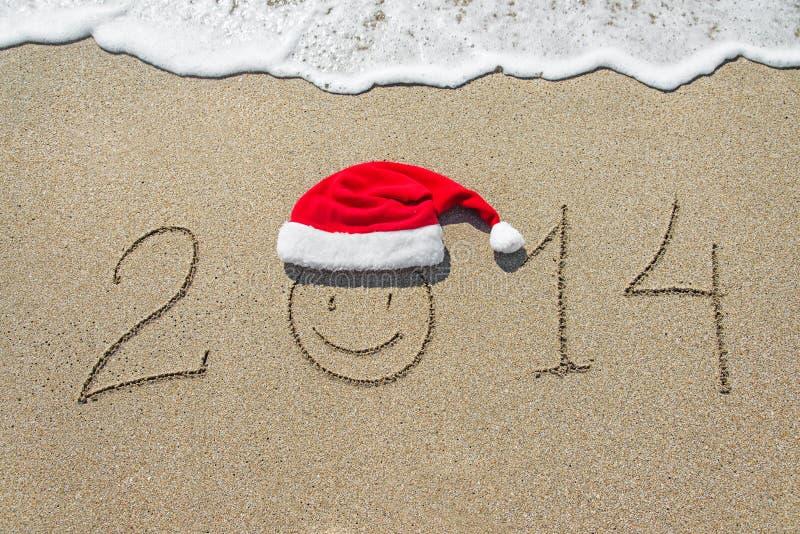 Feliz Año Nuevo 2014 con la cara sonriente en sombrero de la Navidad en b arenoso imagenes de archivo