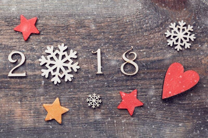 Feliz Año Nuevo 2018 de figuras de madera reales con los copos de nieve y las estrellas en fondo de madera con nieve imagenes de archivo