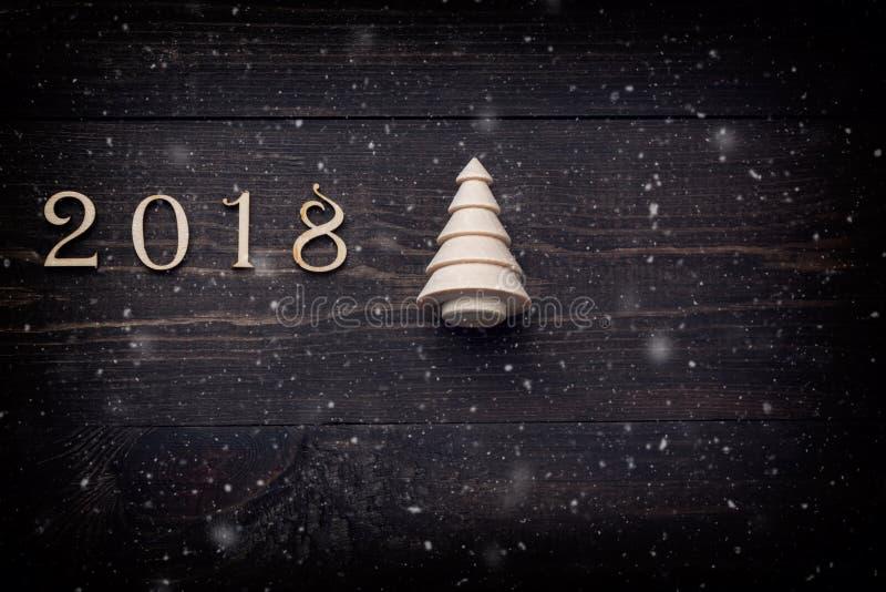 Feliz Año Nuevo 2018 de figuras de madera reales con un árbol de abeto en fondo de madera oscuro con nieve imagenes de archivo