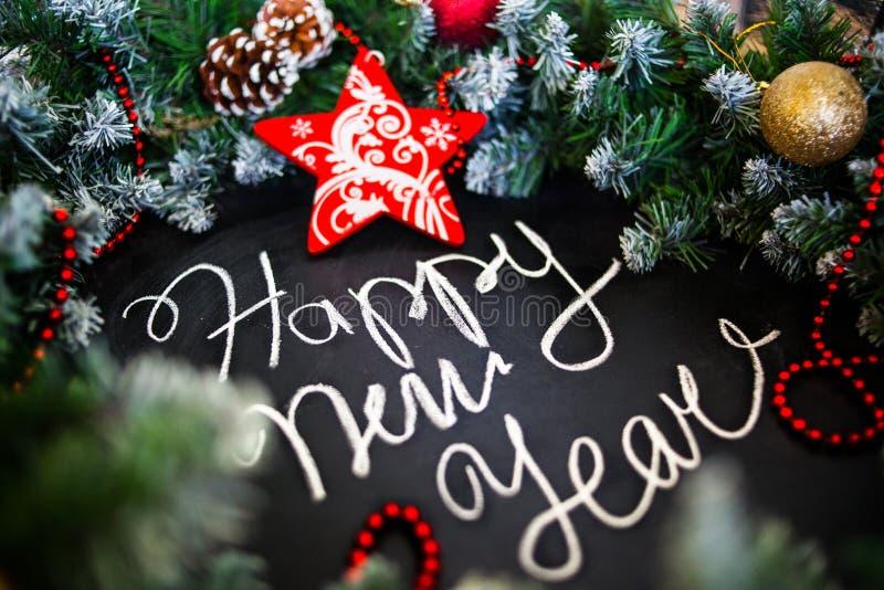 Feliz Año Nuevo de la inscripción en tablero negro Tablero negro con Feliz Año Nuevo de la inscripción de la mano con tiza foto de archivo libre de regalías