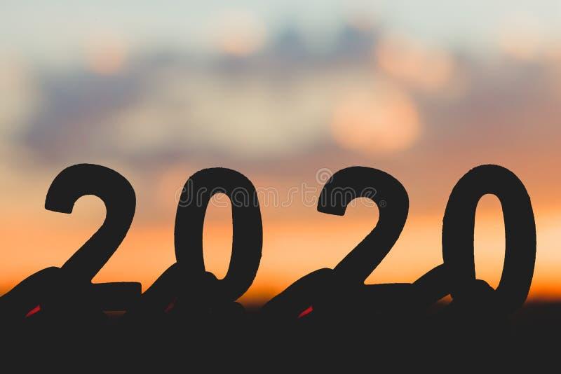 Feliz Año Nuevo de la silueta 2020 de la mano que lleva a cabo el número de madera en el fondo hermoso crepuscular de la naturale imagen de archivo libre de regalías