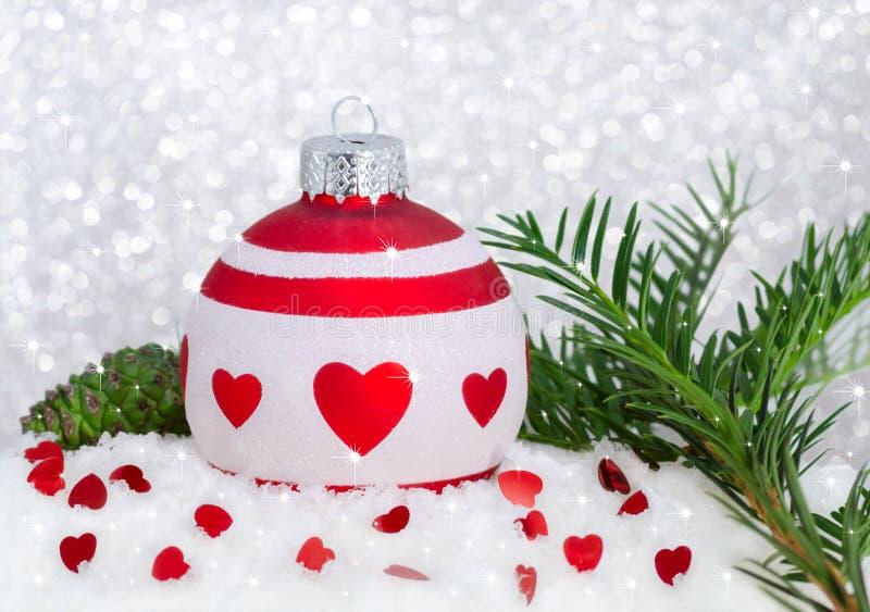 Feliz Año Nuevo de la tarjeta de Navidad con la chuchería, los corazones, el árbol, la nieve, el cono y el bokeh blancos rojos imagen de archivo libre de regalías