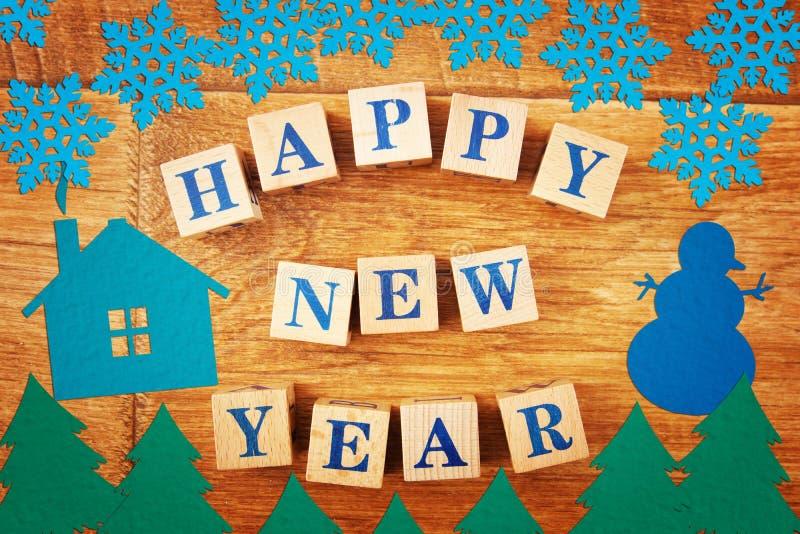Feliz Año Nuevo del texto en los cubos sobre fondo con las figuras de papel coloridas brillantes festivas imagen de archivo libre de regalías