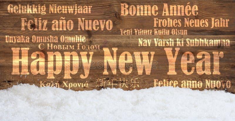 Feliz Año Nuevo en muchas idiomas en fondo de madera nevoso imagen de archivo