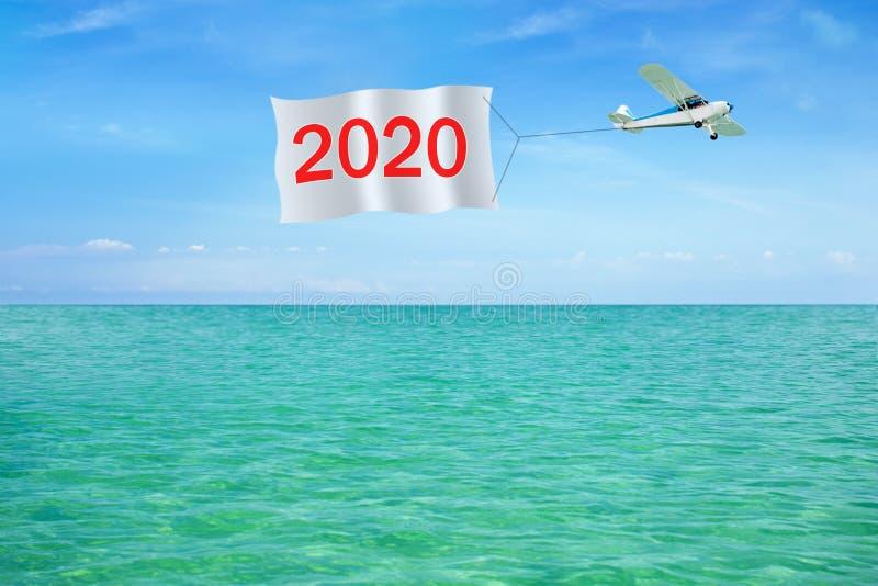 Feliz Año Nuevo 2020 escrita en la bandera que tira del aeroplano en fondo de un cielo y de un mar fotografía de archivo libre de regalías