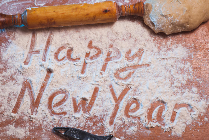Feliz Año Nuevo escrita en la harina, imagenes de archivo