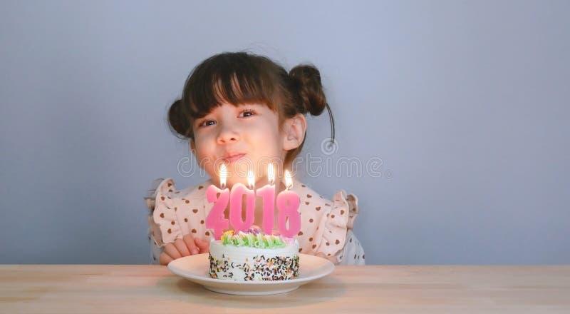 Feliz Año Nuevo 2018 muchacha linda con la cara sonriente con la torta imagen de archivo libre de regalías