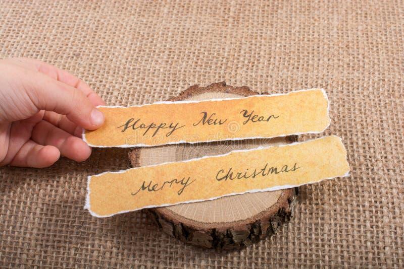 Feliz Año Nuevo, Feliz Navidad, escrita en un papel rasgado fotografía de archivo