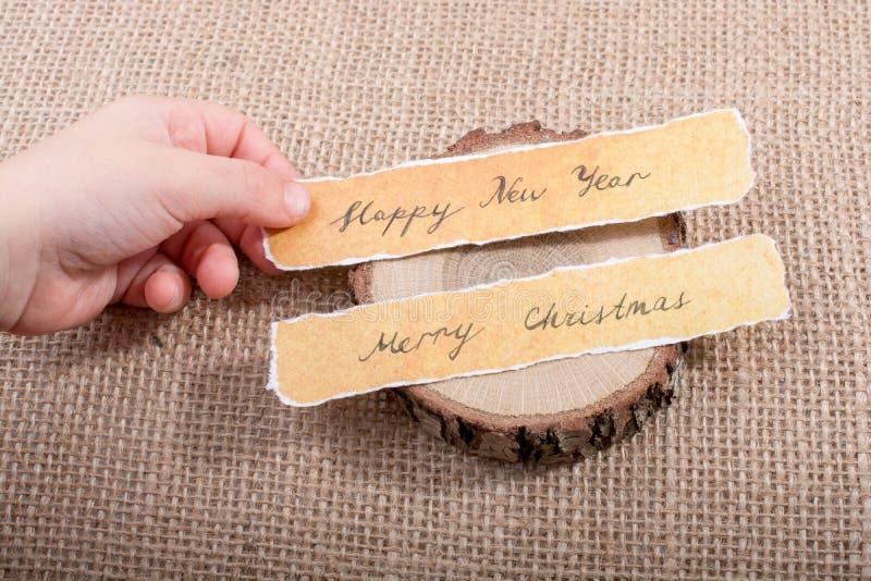 Feliz Año Nuevo, Feliz Navidad, escrita en un papel rasgado fotos de archivo libres de regalías