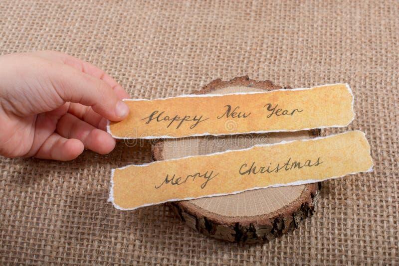 Feliz Año Nuevo, Feliz Navidad, escrita en un papel rasgado imagenes de archivo