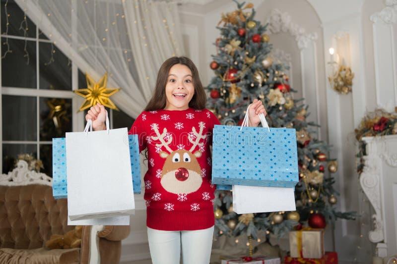Feliz Año Nuevo Navidad Muchacha con los bolsos de compras - sally El niño disfruta del día de fiesta pequeña muchacha feliz en l imagen de archivo libre de regalías