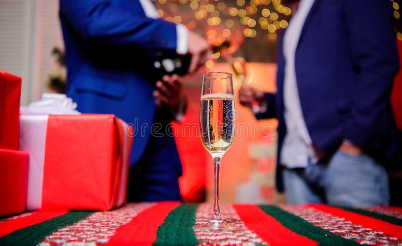 Feliz Año Nuevo y Feliz Navidad E El vidrio llenó el vino espumoso o el champán cerca de las cajas de regalo imagenes de archivo