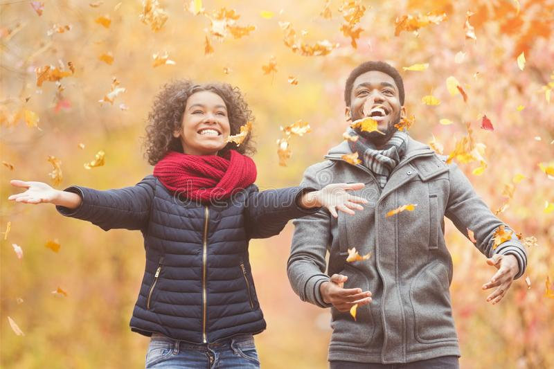 Feliz afro pareja lanzando hojas de otoño imágenes de archivo libres de regalías