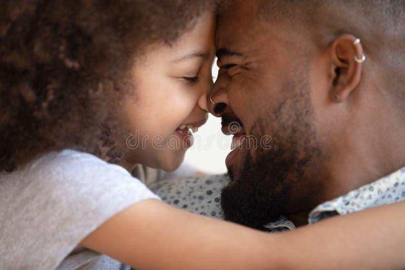 Feliz afroamericano que toca la frente con una hija sonriente imágenes de archivo libres de regalías
