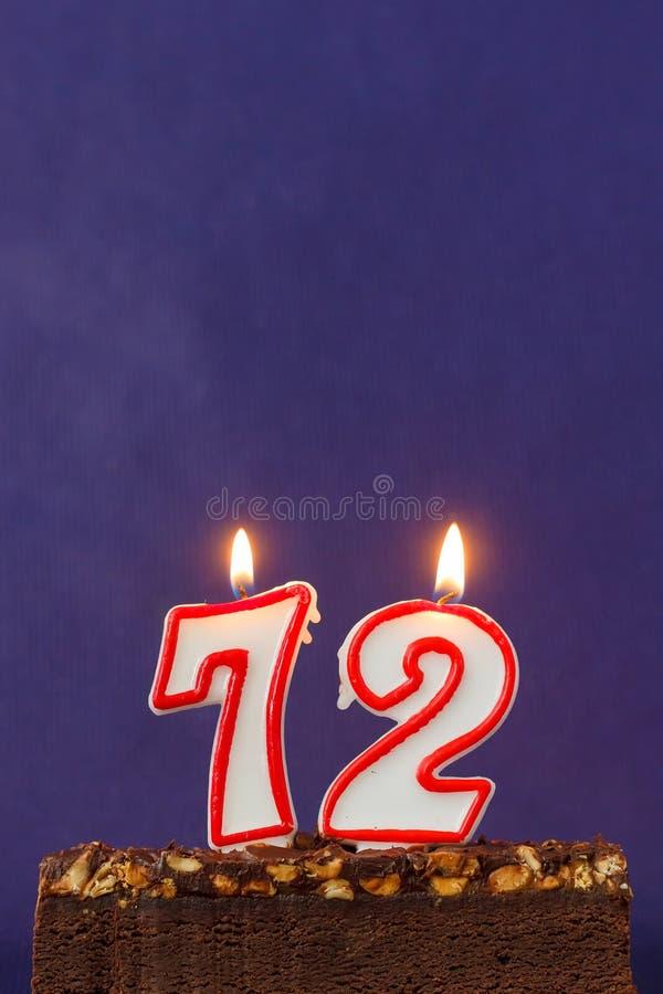 Feliz aniversario Brownie Cake com amendoins, caramelo salgado e velas ardentes coloridas em Violet Background Copie o espa?o par imagens de stock