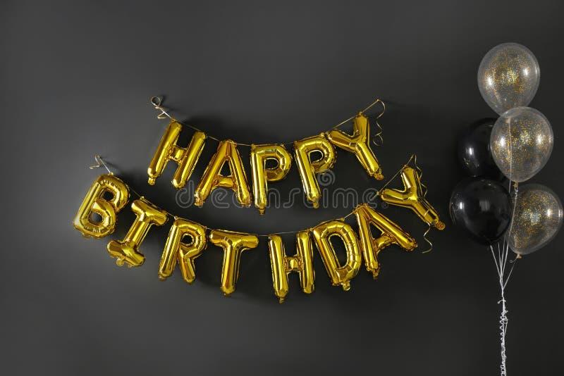 FELIZ ANIVERSARIO da frase feito de letras douradas do balão no preto imagem de stock