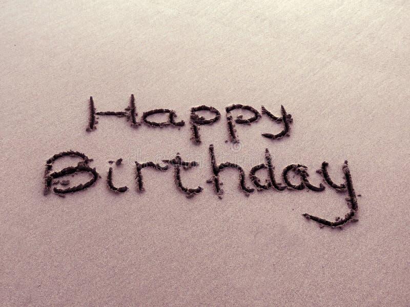 Feliz aniversario escrito na areia fotos de stock
