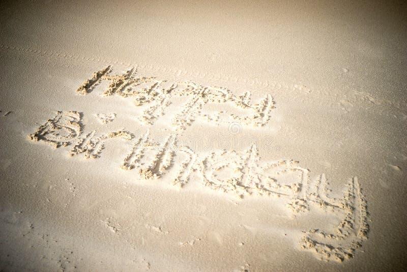 Feliz aniversario escrito na areia foto de stock