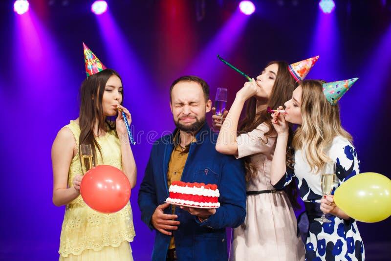 Feliz aniversario Grupo de amigos de sorriso recolhidos junto com o bolo foto de stock royalty free