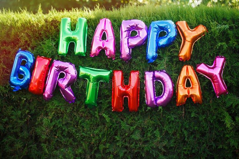Feliz aniversario! A inscrição de balões coloridos, decoração em um partido de jardim festivo no fundo de uma conversão verde fotos de stock royalty free