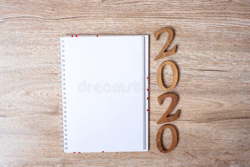 2020 Feliz Ano Novo com caderno em branco para texto e número de madeira na mesa e no espaço para cópia Novo Início, Resolução, O imagem de stock royalty free