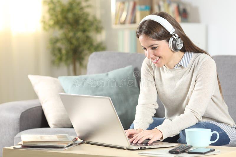 Feliz aprendizaje electrónico de las niñas con laptop y auriculares fotografía de archivo libre de regalías