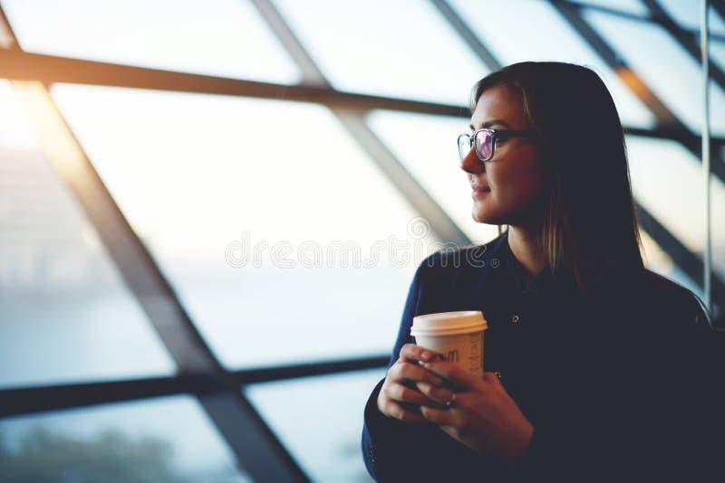 Feliz bonito mantém o café na sala de estar do aeroporto imagens de stock royalty free