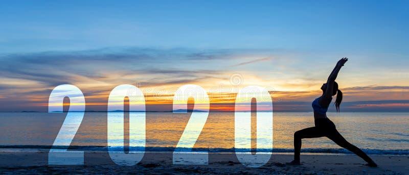 Feliz cartão de ano 2020 Estilo de vida Silhouette mulher ioga praticando ioga como parte do número 2020 perto da praia no pôr do foto de stock royalty free