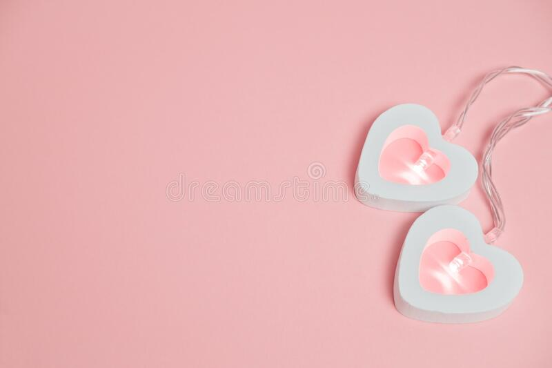 Feliz cartão de boas-vindas do dia dos namorados com luzes de garland e espaço de cópia em um fundo cor-de-rosa imagem de stock