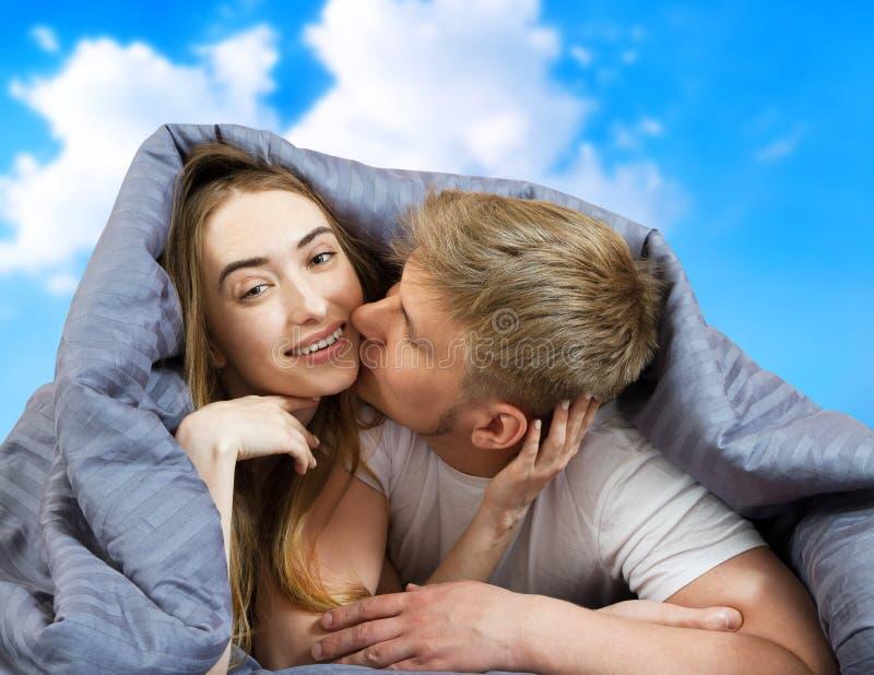 Feliz casal bonito na cama isolado no fundo do céu azul, fique em casa, conceito de quarentena de coronavírus fotos de stock