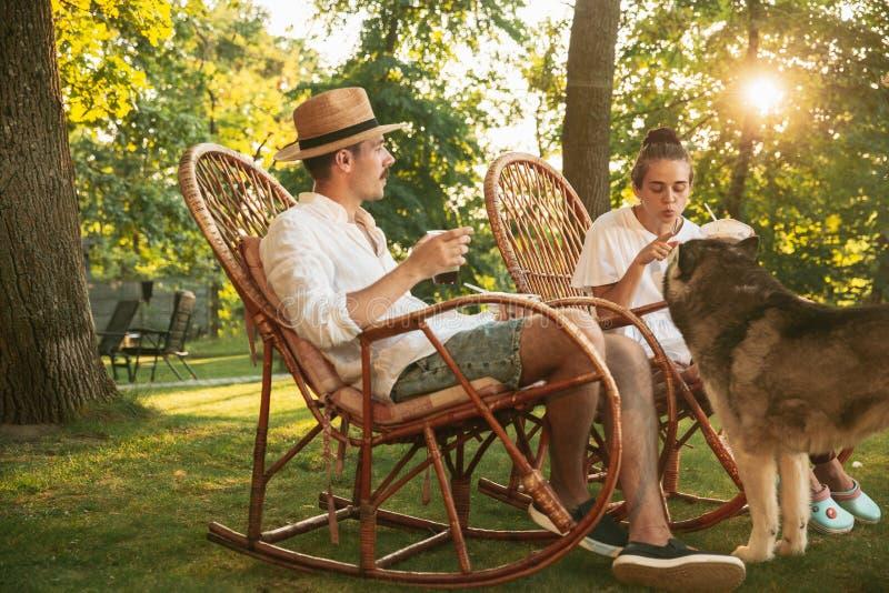 Feliz casal comendo e bebendo cervejas no churrasco, no horário do pôr do sol fotografia de stock royalty free