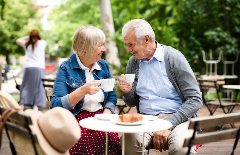 Feliz casal sênior apaixonado sentado ao ar livre no café, falando imagem de stock royalty free