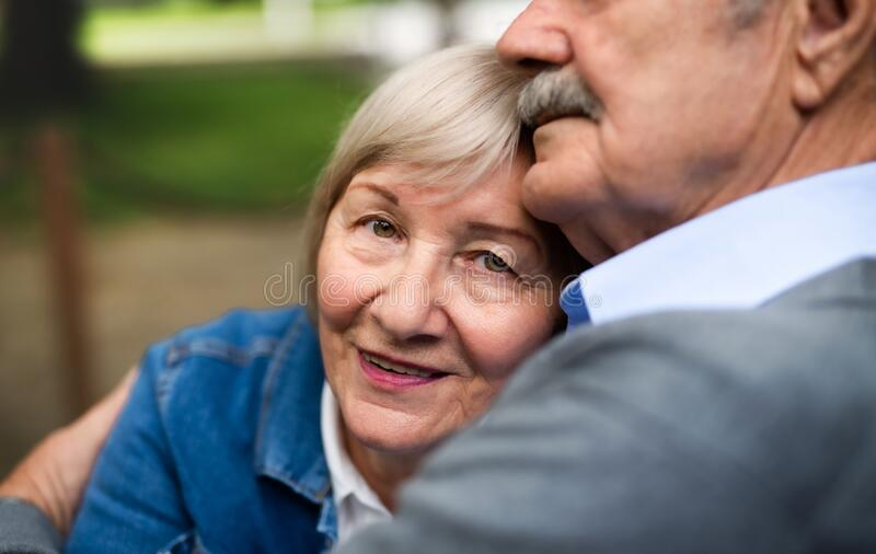 Feliz casal sênior apaixonado sentado ao ar livre, no meio imagem de stock