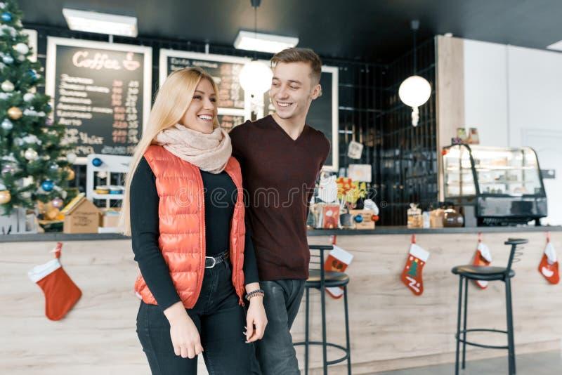 Feliz casal sorridente abraçando na cafeteria na temporada de inverno imagem de stock royalty free