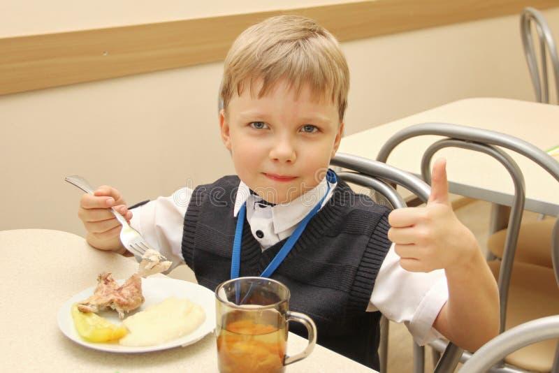 Feliz colegial que se sienta en la tabla en la cafetería de la escuela que come la comida pulgares de consumición para arriba - R fotografía de archivo