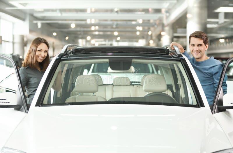 Feliz com seu carro novo. Pares novos felizes que estão em ambos o si foto de stock
