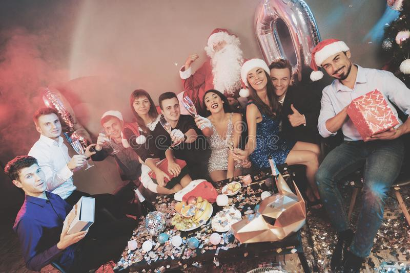 Feliz compañía en el partido del ` s del Año Nuevo Regalos del champán y del intercambio de la bebida de la gente imagen de archivo libre de regalías