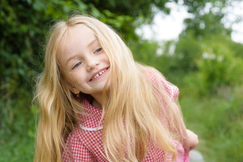 Feliz con las cosas simples Pelo largo del desgaste de la niña Pequeña muchacha con el pelo rubio Pequeño niño feliz con adorable imágenes de archivo libres de regalías