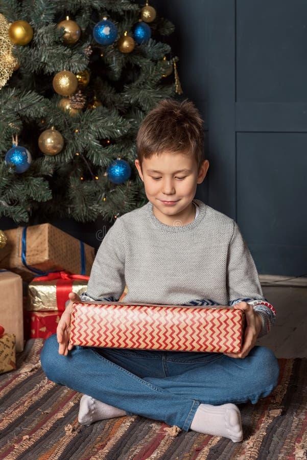 Feliz con una sonrisa pacífica que un muchacho se sienta cerca del árbol de navidad y que considera una caja de regalo en casa fotos de archivo