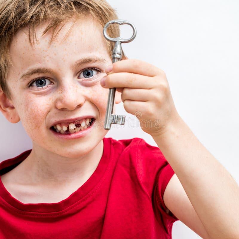 Feliz creciendo al muchacho que muestra la llave para el ratoncito Pérez de la diversión imagenes de archivo