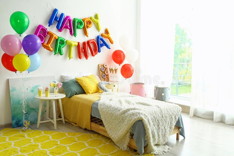 FELIZ CUMPLEAÑOS de la frase hecho de letras y de la tabla coloridas del globo con las invitaciones en dormitorio fotos de archivo libres de regalías