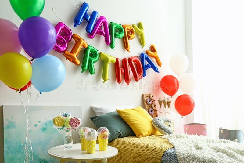 FELIZ CUMPLEAÑOS de la frase hecho de letras y de la tabla coloridas del globo con las invitaciones en dormitorio imagen de archivo libre de regalías